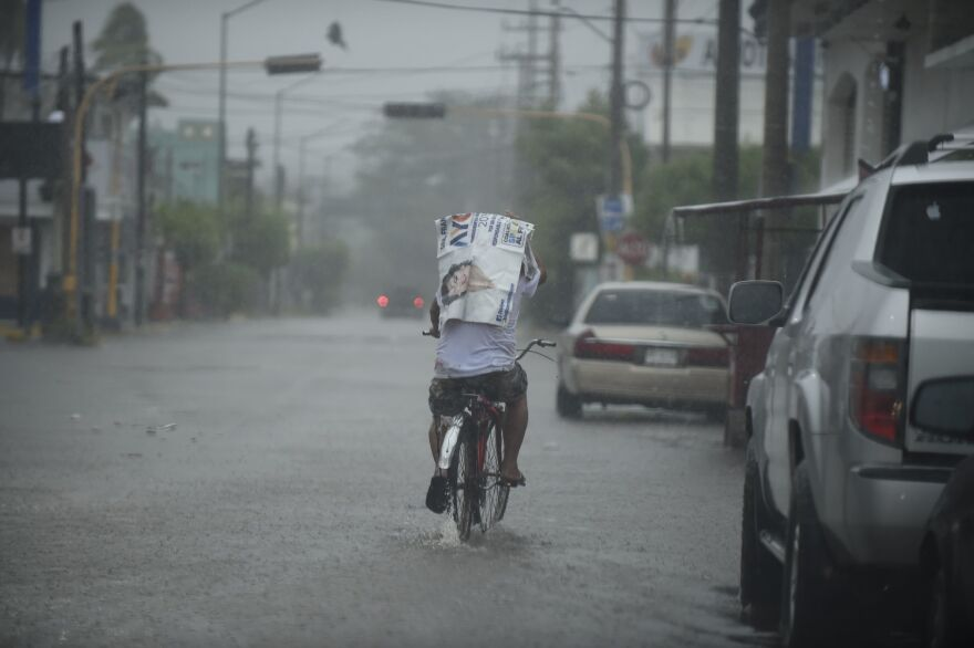A man rides his bike along a street as Hurricane Willa arrives to Escuinapa, Sinaloa state, on Tuesday.