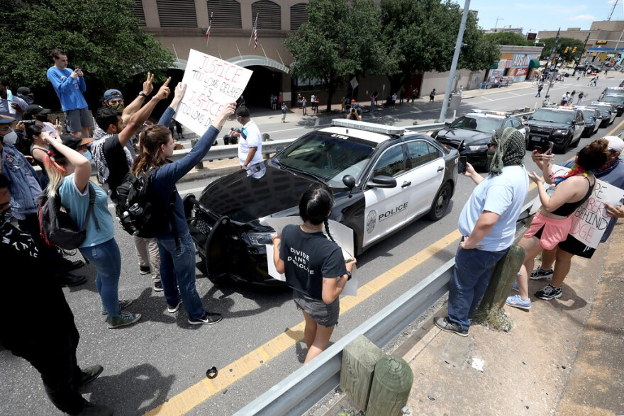 Protesters prevent a line of Austin Police vehicles from driving onto Interstate 35.