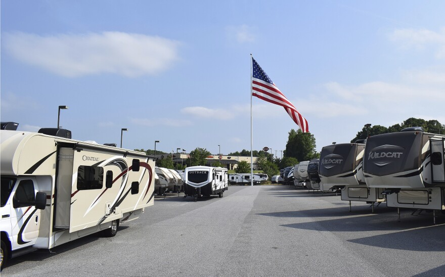 A giant American flag that's been at the center of a local controversy blows in the wind at Gander RV, in Statesville, N.C. The North Carolina city has voted against the flying of really big flags, holding its ground against reality TV star Marcus Lemonis' huge Stars and Stripes. (Jennifer Munday/Camping World via AP)