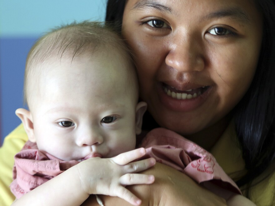 Thai surrogate mother Pattaramon Chanbua poses last August with Gammy, then nine months old. The boy, who has Down Syndrome, was rejected by the Australian couple who contracted Pattaramon for the birth.
