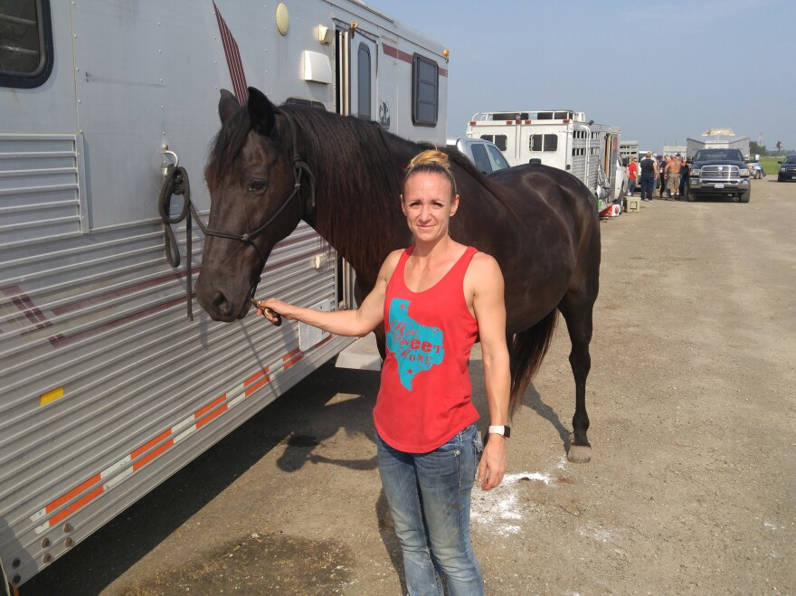 Amy Walters from Copperas Cove, Texas, with a horse she rode as she rounded up lost cattle and brought them to the makeshift shelter in Beaumont, Texas.