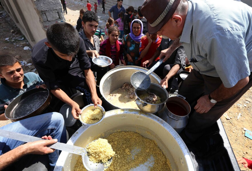 Iraqi Yazidi families who fled the violence in their hometown of Sinjar are given food at a school where they are taking shelter in the Kurdish city of Dohuk on Tuesday.