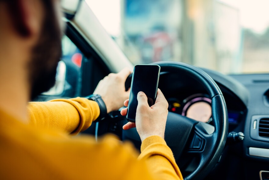Photo of person texting and driving.