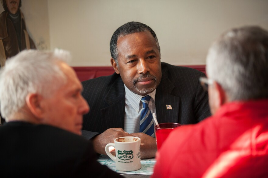 Republican presidential candidate Ben Carson has coffee with staff members during a campaign stop at The Airport Diner in Manchester, N.H.