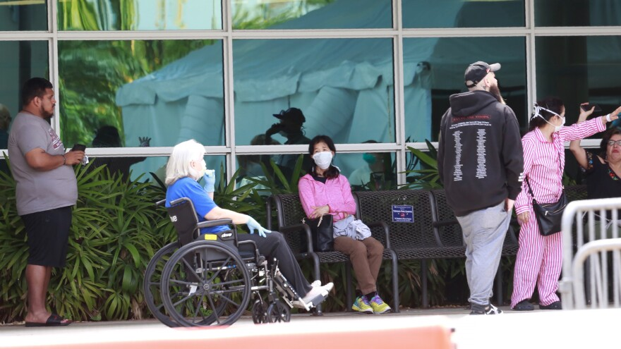 Patients wait to be seen at a medical testing site, set up amid the virus outbreak at Memorial Hospital West in Pembroke Pines, Tuesday, March 17, 2020, in Pembroke Pines, Fla.