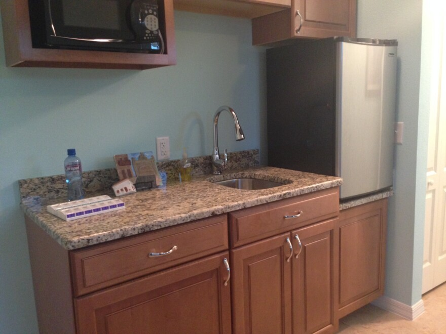 The kitchenette has a raised-up mini-fridge, low cabinets with handles and a lowered sink.