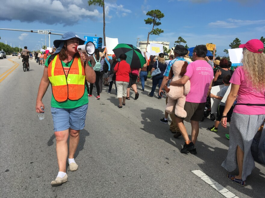 An official guides protesters down 288th Street, in Homestead, Fl., telling them to stay on the right side of the road