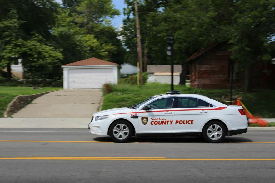 A St. Louis County Police car drives through the frame with its lights on.