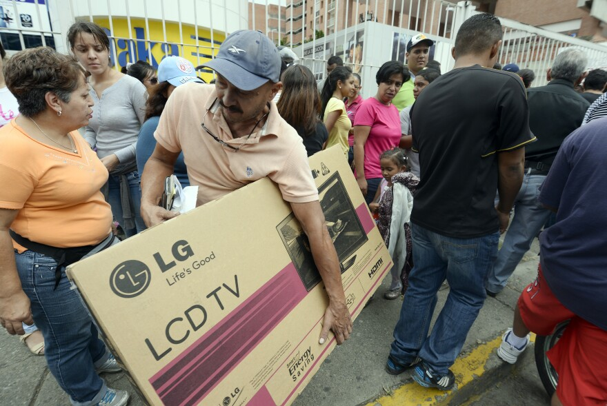 Shoppers loaded with purchases leave a Daka store in Caracas on Saturday.