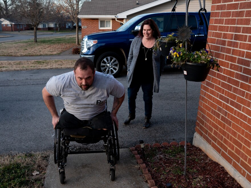 Retired Sgt. Chris Kurtz wheels himself up to his front door as his wife and caretaker, Heather Kurtz, follows behind. The Department of Veterans Affairs told him last summer that he no longer needs a caregiver.