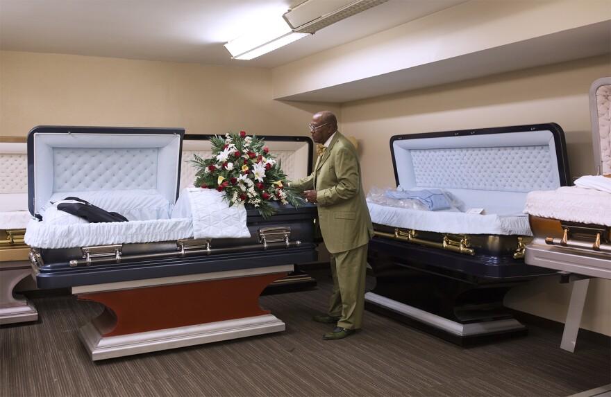 Ronald Jones adjusts a casket in his funeral home's display room. (May 16, 2018)