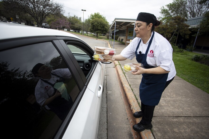Rosa Montalvo, a cafeteria employee, delivers food to parents parked outside Dawson Elementary school.