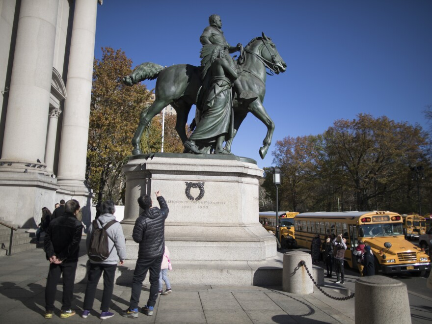 New York Mayor Bill de Blasio backs a decision to remove the statue of Theodore Roosevelt in front of the American Museum of Natural History in New York. Visitors look at a statue which includes a man in a Native American headdress.