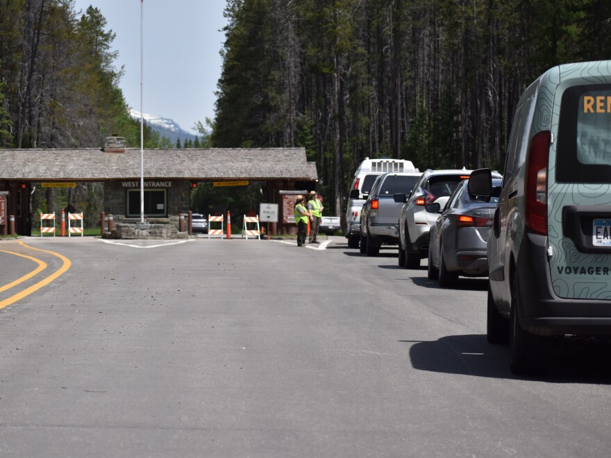 Cars line up at the west entrance into Glacier National Park on June 12. Montana is welcoming nonresidents back to the state.