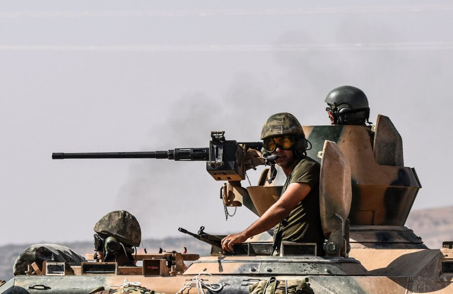 Turkish soldiers sit on a tank driving to Syria from the Turkish-Syrian border city of Karkamis on Saturday. Turkey's army has launched an operation in northern Syria to drive Islamic State fighters out of the border area.