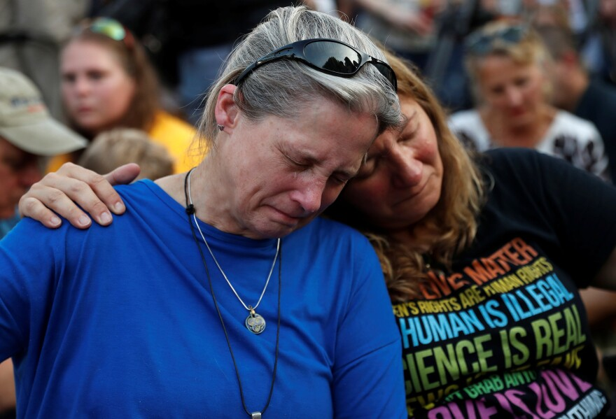 Community members Carol Geithner, left, and Yasemine Jamison take part in a candlelight vigil near the Capital Gazette, the day after a gunman killed five people inside the newspaper's building in Annapolis.
