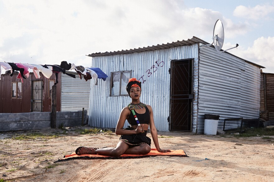 "Mthulic Vee Vuma, a 21-year-old studying public management at West Coast College, wears traditional Xhosa clothing and jewelry in front of a shack in Khayelitsha. ""The meaning of the clothing I am wearing is to love and accept our culture,"" Vuma says. Her family initially struggled to accept her as a trans woman, believing it was a curse, but she says they now give her total support."