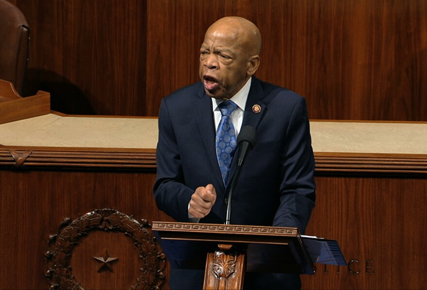 Rep. John Lewis, D-Ga., speaks as the House of Representatives debates the articles of impeachment against President Trump this month. Lewis says he'll stay in office while he undergoes treatment for pancreatic cancer.