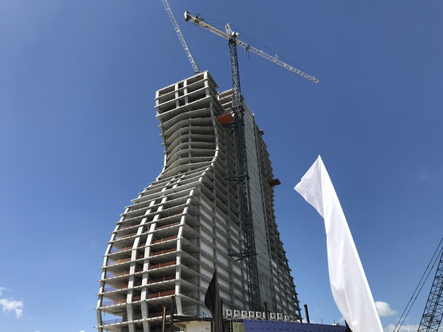 The final steel beam of the hotel's main structure was placed at the top of the guitar Monday, with the Seminole Tribe flag, American flag and Florida flag.