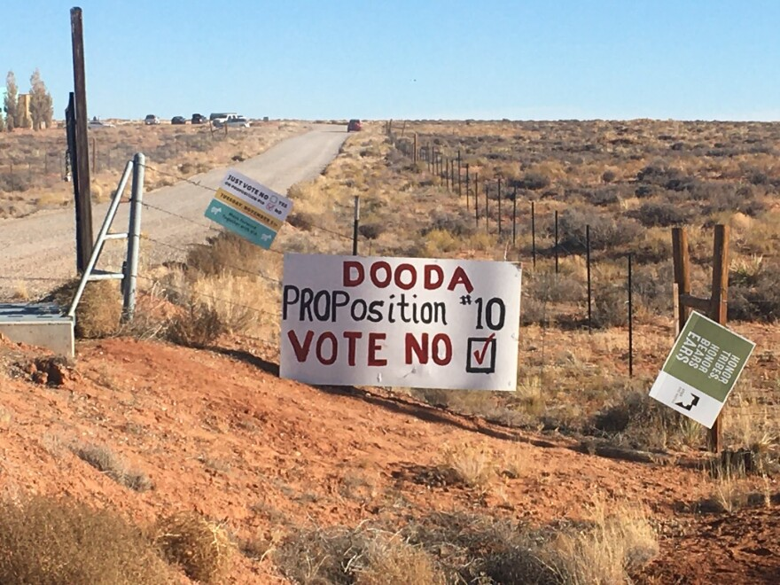 """Photo of a hand painted sign on a gate that says """"Dooda, proposition 10, vote no."""""""