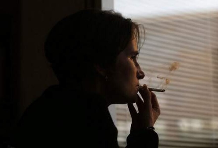 Person smoking near a window.