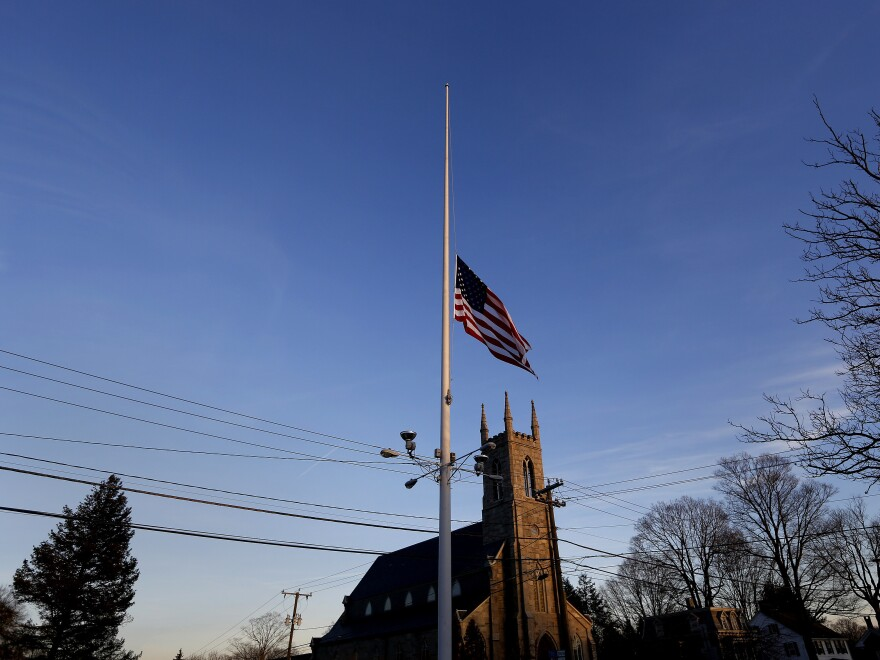 A flag is seen at half-staff along Main Street in Newtown, Conn., on Friday after a mass shooting that left at least 28 dead, including the suspected gunman.