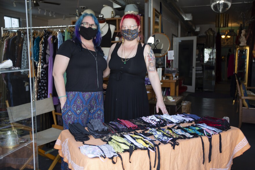 Two women with blue and pink hair wearing masks stand at the entrance to their store behind a table covered with cloth masks.