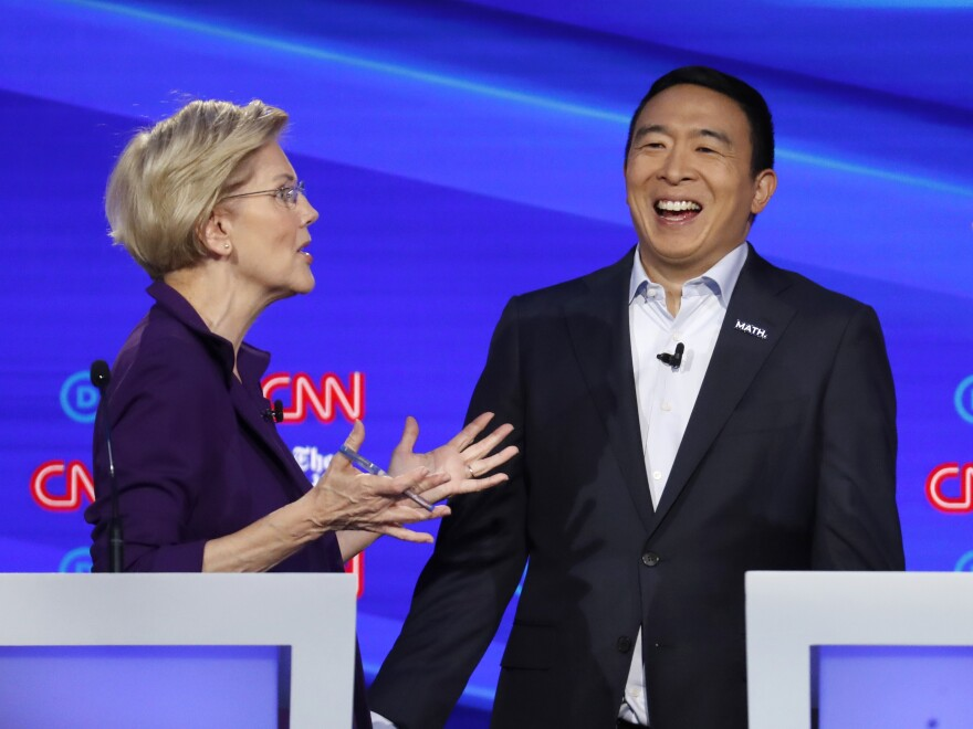 Sen. Elizabeth Warren, D-Mass., and entrepreneur Andrew Yang talk during a break in the Democratic presidential primary debate hosted by CNN/<em>New York Times</em>.