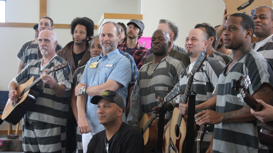 The 2010 launch of Jail Guitar Doors in Austin, Texas.  With Boots Riley (fourth from left, in jacket), Wayne Kramer (center, in blue), Dave Gibbs (in hat) and Tom Morello (kneeling in foreground).