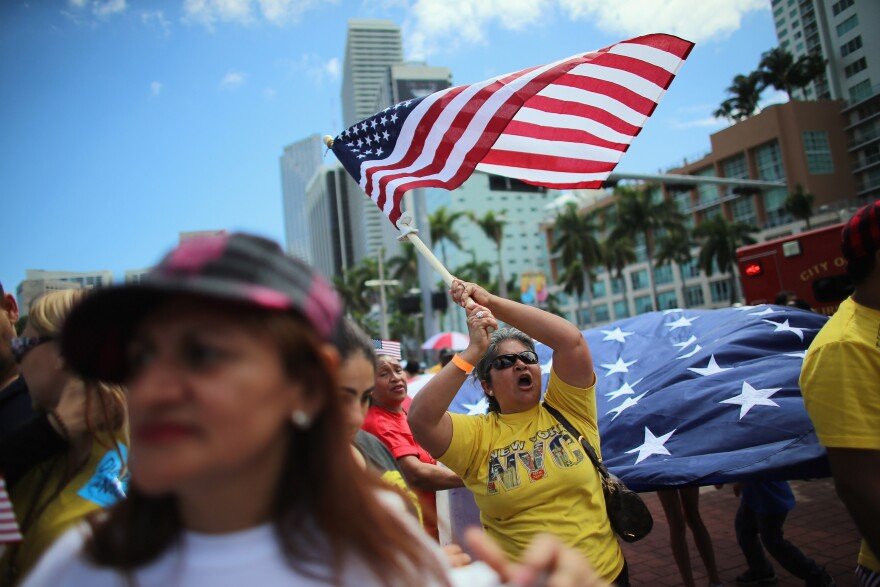Maglena Gomez waves an American flag as she and others participate in a march that organizers said was an attempt to get the U.S. Congress to say yes to immigration reform on April 6, 2013 in Miami, Florida.