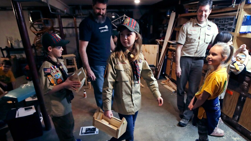 """Tatum Weir (center) carries a tool box she built as her twin brother, Ian (left), follows after a Cub Scout meeting in Madbury, N.H., on March 1. For more than a century, the Boy Scouts of America's flagship program for older boys has been known as the Boy Scouts. With girls soon entering the ranks, the name will change to """"Scouts BSA."""""""