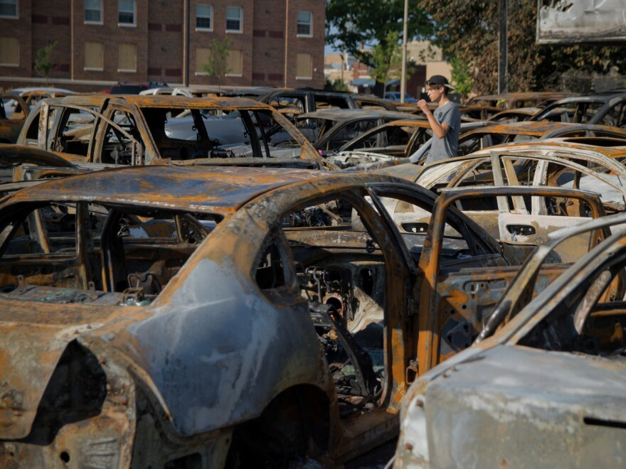 A young man walks through the lot of a Kenosha car dealership that was burned during Sunday night's protests over the police shooting of Jacob Blake.