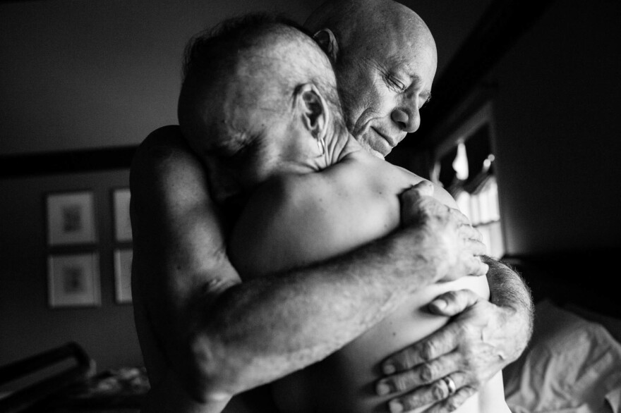 Dad and Mom embrace in the bedroom of their home. They never could have imagined both being in treatment for cancer at the same time. Together, they faced the daily struggles of illness in their own lives while also caring for each other.