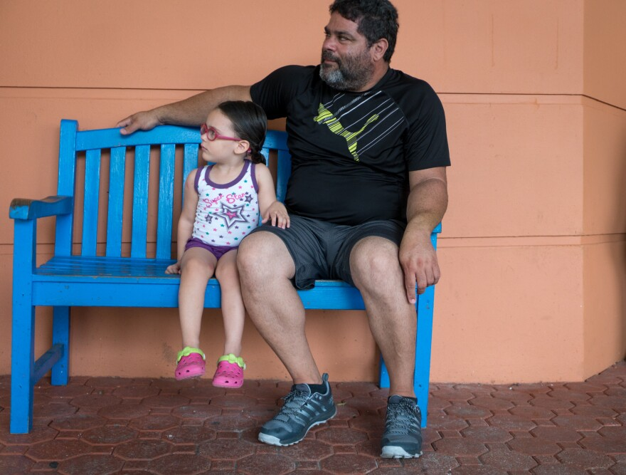 Angelica Alicea, 3, and her grandfather Julio Alicea wait outside the San Jorge Children's Hospital.