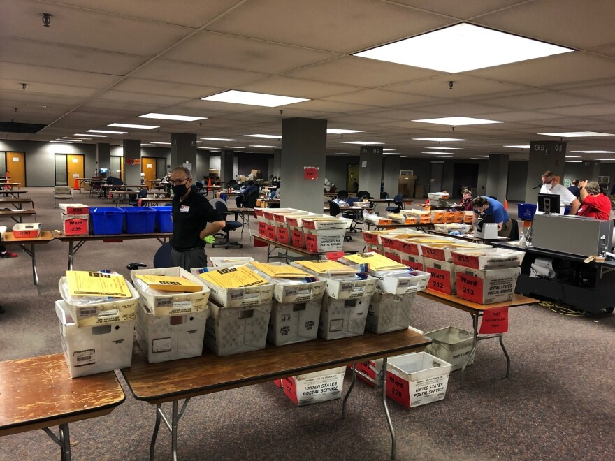 Crates full of absentee ballots that were mailed in or placed into secure ballot drop boxes await to be processed by election officials in Milwaukee on Tuesday.