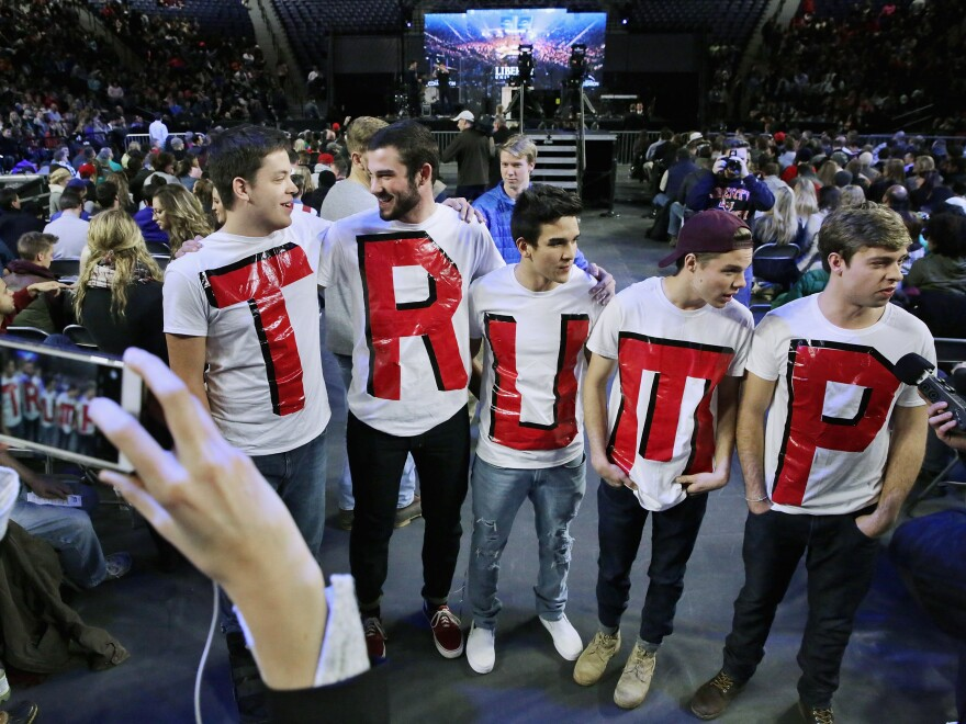 """Liberty University students (from left) Austin Miller, James Ford, Jeremy Boyd, Josiah O'Boyle and Cody Hildebrand wear """"TRUMP"""" shirts while waiting to hear the Republican presidential candidate."""