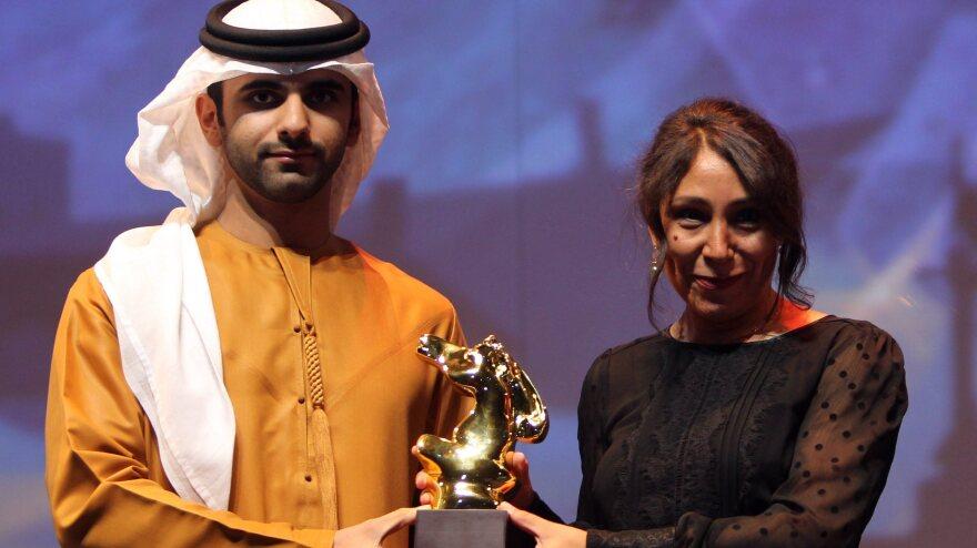 Saudi Arabia film director Haifaa Al-Mansour (right) receives the award of best film for her movie <em>Wadjda</em> at Dubai International Film Festival in Dubai, United Arab Emirates, on Dec. 16, 2012.