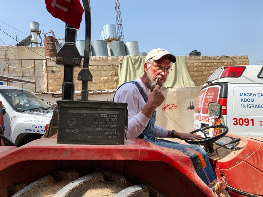 Chicago native and Hebron settler Yisrael Zeev is in costume as a pipe-smoking farmer and driving a float in the Purim parade. A red swath from the uniform of an international observer from the recently expelled Temporary International Presence in Hebron flutters on a pole.