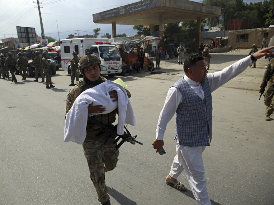 An Afghan security officer carries away a baby after an attack Tuesday on a hospital's maternity section in Kabul.