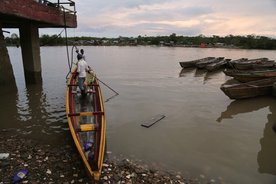 Men in the city of Quibdó prepare the motorboat they use to make the hours-long river journey to a cacao community. Most Chocó farmers live in riverside communities far from Quibdó and must travel there to sell their crops — by motorboat, because the villages lack roads.