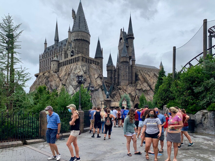 Spread out crowds of people wearing masks standing in front of Hogwarts Castle at Universal Orlando Resort.