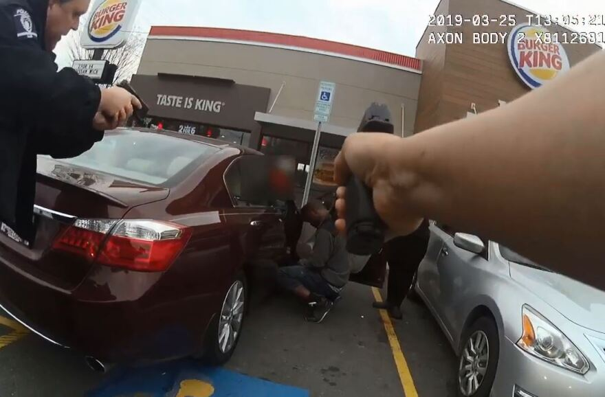 A still from CMPD body-cam footage shows Danquirs Franklin squatting next to a car in a Burger King parking lot on Beatties Ford Road.