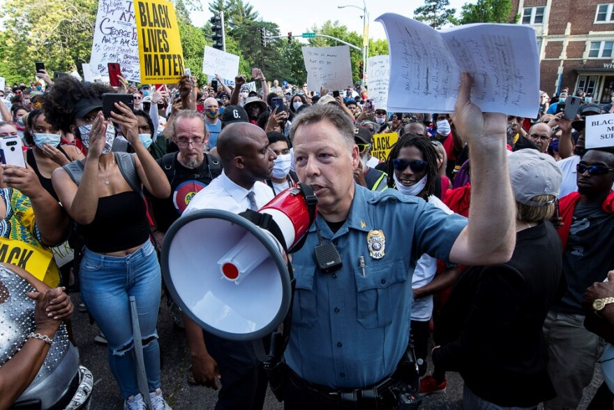 Kansas City police Chief Rick Smith holding a bullhorn and addressing a crowd of protesters.