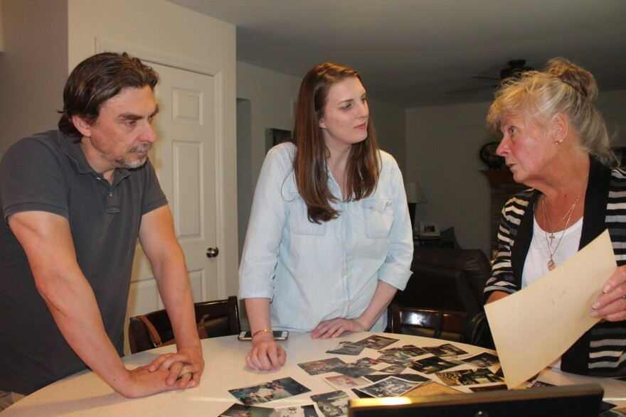 Filmmakers Geoff Story and Beth Prusaczyk are looking at old photos with Buddy Walton's niece Susie Seagraves.