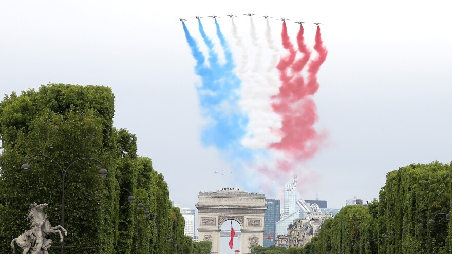 The French elite acrobatic flying team Patrouille de France performs a flying display of the French national flag over the Arc de Triomphe during the annual Bastille Day military ceremony in Paris on Tuesday.