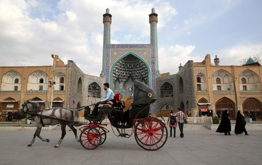 People ride a horse and carriage through Isfahan's central square in June 2014. With its immense mosques, picturesque bridges and ancient bazaar, the city is a virtual living museum of Iranian traditional culture and is a top tourist destination. After decades of difficult relations with the West, Iran now says it wants more foreign tourists, including Westerners.