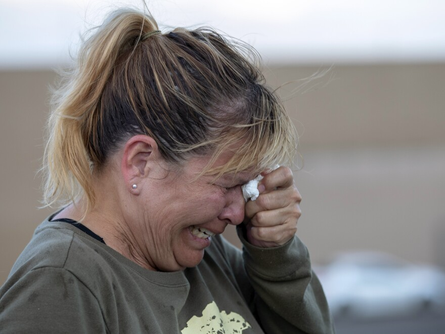 Edie Hallberg cries while speaking to police outside Walmart, where a shooting occurred earlier in the day, as she looks for her missing mother, Angie Englisbee, who was in the store during the attack in El Paso, Texas.