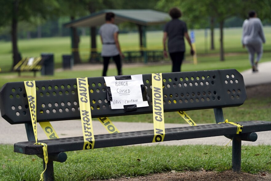 A park bench is cordoned off Wednesday, March 25, 2020, in Houston.