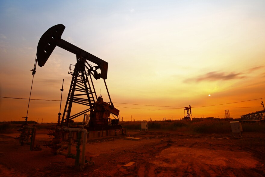 A photo of an oil pump into front of a sunset background.