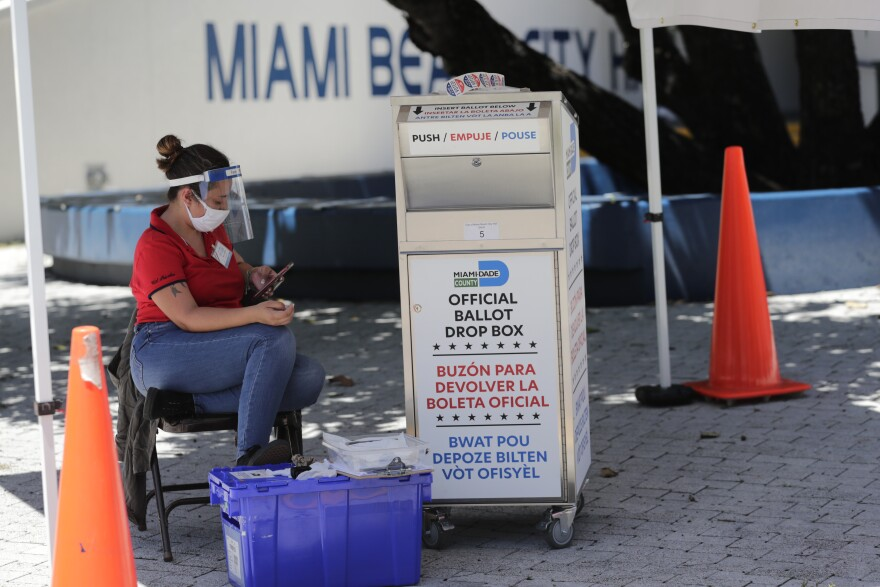 A poll worker wears personal protective equipment as she monitors a ballot drop box for mail-in ballots outside of a polling station during early voting, Friday, Aug. 7, 2020, in Miami Beach, Fla. Florida's primary election is August 18.